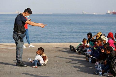 En politimann snakker med båtflyktninger etter at de gikk i land i Augusta på Sicilia 30. juni.