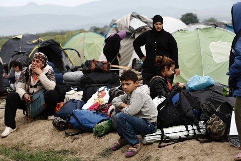 En flyktningfamilie venter på å bli transport videre av gresk politi i forbindelse med tømming av den midlertidige flyktningleiren i Idomeni på grensen til Makedonia 24. mai i år.
