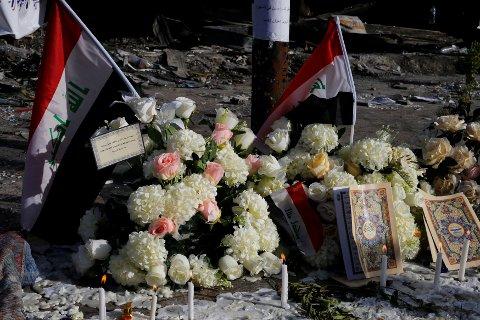 Blomster og lys står på gaten ved bombestedet til minne om ofrene i Karrada i Bagdad.