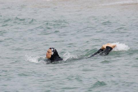 En kvinne bader i burkini i Marseille. Badedrakten dekker hele kroppen med unntak av ansikt, hender og føtter.