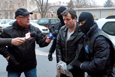 Marcel Lazar Lehel eskortes av maskerte politimenn i Bucarest i Romania 22. januar 2014.