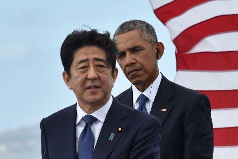 USAs president Barack Obama lytter mens Japans statsminister Shinzo Abe taler på den amerikanske marinebasen Pearl Harbor på Hawai tirsdag.