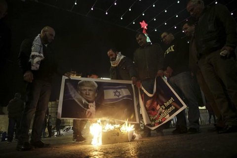 Palestinian hold poster of the U.S. President Donald Trump during a protest in Bethlehem, West Bank, Tuesday, Dec. 6, 2017. President Trump forged ahead Tuesday with plans to recognize Jerusalem as Israel's capital despite intense Arab, Muslim and European opposition to a move that would upend decades of U.S. policy and risk potentially violent protests. (AP Photo/Mahmoud Illean)