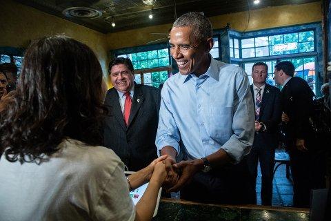 Tidligere president Barack Obama hilser på en kaféeier i Illinois, hvor han har drevet valgkamp for Demokratene i forkant av mellomvalget neste uke.