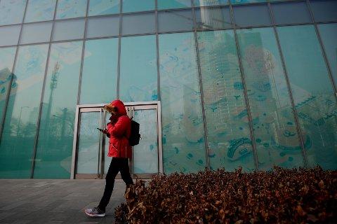 En mann går forbi tomme kontorlokaler i Beijing. Kinas økonomi sakker farten etter handelskrigen med USA og tyngre gjeldsproblemer. Illustrasjonsfoto: Andy Wong / AP / NTB scanpix