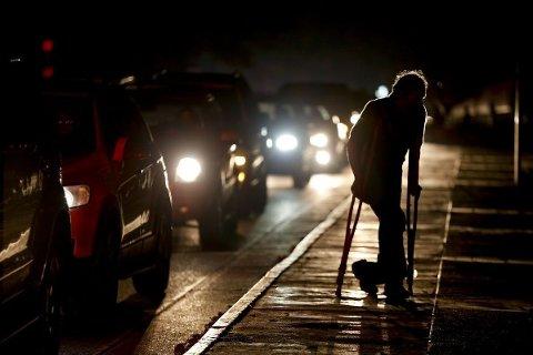 I helgen har det vært en rekke strømbrudd i Venezuela. Her går en mann gatelangs i den mørklagte hovedstaden Caracas fredag, hvor de eneste lysene som finnes kommer fra bilene.