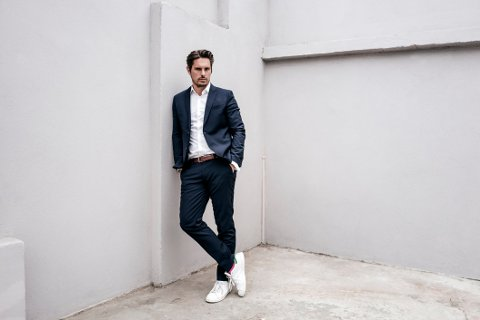 Portrait of confident businessman leaning against a wall