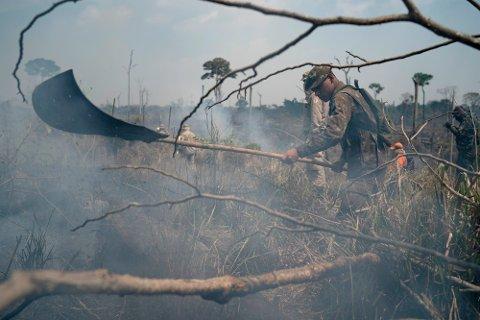 En brasiliansk soldat jobber med brannslukking i et område i Nova Fronteira-regionen i Novo Progresso i Brasil i forrige uke. Satellittdata viser økende luftforurensing i landet. Foto: Leo Correa / AP / NTB scanpix