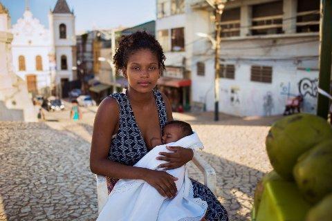 """Salvador, Brazil: """"Når jeg tenker på Rachel får jeg lyst til å gråte"""", skriver Noroc. Femten år gammel var Rachel allerede mor til en liten jente. Faren ble brutalt drept bare uker før fødselen. Både gjengvold, narkotikamisbruk og tenåringsmødre er vanlig der hun bor. Rachels mor var rusavhengig og forlot familien tidlig. Rachels far, en gatefeier, oppdro henne alene og hjelp henne å komme i gang med en liten juice-stand så hun kan tjene til livets opphold for seg selv og datteren. """"Den andre dagen jeg besøkte henne gråt hun fordi hun hadde bare solgt to juicer på noen timer, og hun var sliten - barnet hadde holdt henne våken hele natten. Men når hun snakket om datteren smilte hun. Hver eneste dag, etter en lang reise hjem, koker hun vann for å vaske datteren og klærne for hånd. Hver dag er babyens klær skinnende rene. Rachel er en ekte heltinne. Selv om hun er ung, så er hun også elskelig og usedvanlig sterk"""", skriver Noroc."""