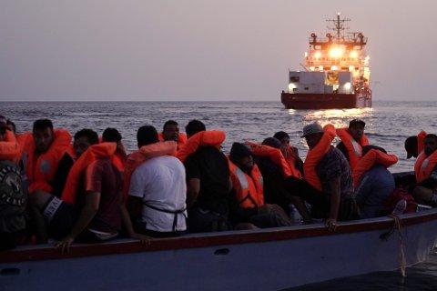 KOMMER FOR Å KUNNE SENDE PENGER HJEM:Rapporten viser at den viktigste grunnen til at folk reiser fra afrikanske land til Europa, er at de ønsker å tjene penger til familien. Illustrasjonsfoto: Migranter i en overfylt trebåt venter på å bli plukket opp i Middelhavet.
