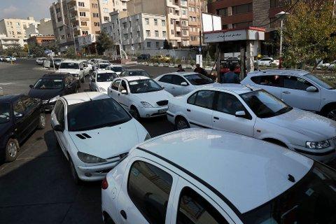 Flere biler står i kø for å fylle bensin i Teheran i Iran fredag. Myndighetene økte uventet bensinprisene, noe som har ført til flere demonstrasjoner.
