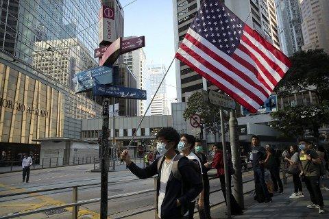 HONGKONG KASTER SKYGGER OVER HANDELSSAMTALER: Begge kamre i Kongressen i USA har vedtatt et lovforslag som støtter demonstrantene i Hongkong. Her flagger en demonstrant med den amerikanske flagget i finansdistriktet i Hongkong onsdag. Foto: