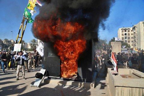 ANGREP USAS AMBASSADE: : Titalls tilhengere av irakisk sjiamilits klarte å bryte seg gjennom den ytterste veggen ved USAs ambassade i Bagdad tirsdag. De fleste andre nøyde seg med å protestere og sette fyr på ting utenfor.