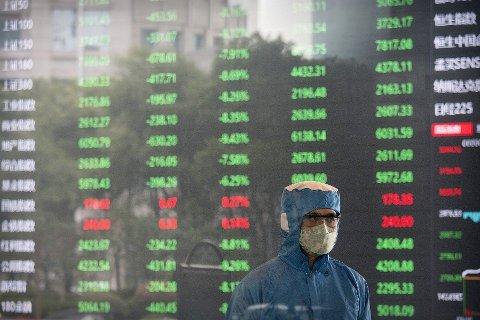 VOLATILE TIDER: En ansatt med ansiktsmaske og drakt står foran storskjermen i lobbyen til Shanghai Stock Exchange mandag 03.02.20.
