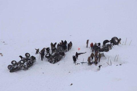Redningsarbeidere graver i snøen ved tre kjøretøy som alle ble tatt av et snøskred ved byen Bahcesehir i provinsen Van øst i Tyrkia onsdag. Foto: DHA via AP / NTB scanpix