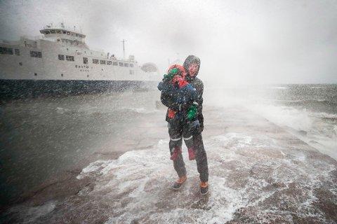 Dmitrij Gordejev og sønnen Daniel på fem år i sjøsprøyt og regn ved ferjekaia i Moss søndag ettermiddag. I bakgrunnen ligger en av ferjene som ble innstilt på ruten mellom Horten og Moss.