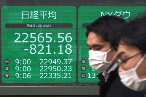 BUNNLØST: Folk med munnbind haster forbi en informasjonstavle som viser torsdagens nedgang for den japanske Nikkei-indeksen. Fredag fortsatte fallet og indeksen falt over 3 prosent fra start. Foto: Eugene Hoshik/ AP/ NTB scanpix