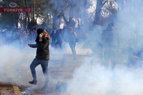TÅREGASS: En migrant dekker ansiktet sitt mens tåregassen fyller luften under sammenstøtet med gresk politi lørdag morgen.