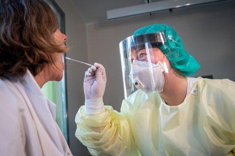 Fagutviklingssykepleier Marte Rygh Selmer ikledd smittevernutstyr tar en spyttprøve på isolatposten på Ullevål sykehus. Bildet er tatt før det første korona-tilfellet ble registrert i Norge.