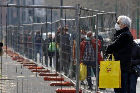 SITUASJONSBILDE fra Milano fredag, hvor folk holdt god avstand i køen for å bli sluppet inn på et supermarked. Italia topper nå lista over koronadødsfall i verden og har flest aktive smittetilfeller.