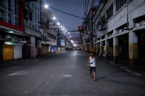 En filippinsk mann avbildet i de tomme gatene i hovedstaden Manilla under unntakstilstanden på Filippinene.