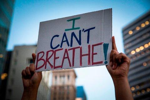 DEMONSTRERER: En demonstrant holder opp en plakat under i Oakland i California onsdag. I flere dager på rad har det vært demonstrasjoner mot politivold og rasisme i amerikanske storbyer i kjølvannet av Georg Floyd-saken.