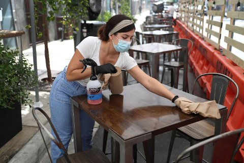 UTESERVERING: Katrina Tico tørker bordene og gjør klar for uteservering på en restaurant i Wynwood i Miami i Florida torsdag. Serveringsstedene har blitt bedt om å stenge for servering inne som et tiltak mot smittespredning.