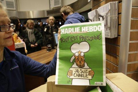 """Folk sto i lang kø i Narvesen Continental i Oslo for å forsøke å få tak i et av de 200 eksemplarer av det franske satiremagasinet Charlie Hebdo som var tilsalgs i 2015. Her sees ukemagasinets forside som viser profeten Muhammed som gråter og holder opp et skilt hvor det står """"jeg er Charlie""""- """"Je suis Charlie"""" - og """"alt er tilgitt """"- """"Tout est pardonne""""."""