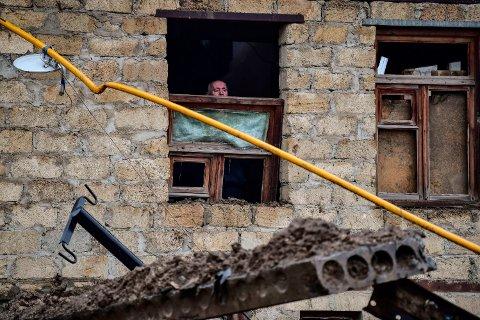 TØFFE TIDER: En eldre mann i byen Stepanakert i Nagorno Karabakh titter ut på elendigheten rundt ham fra sitt krigsskadde hus.