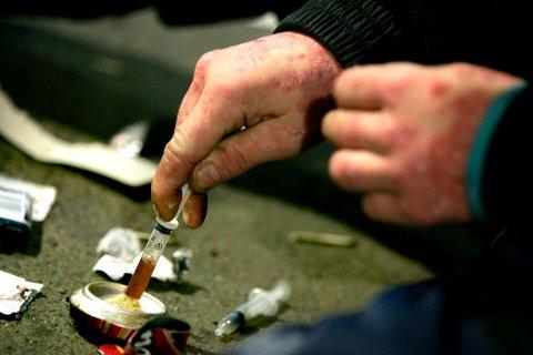 OVERDOSEDØD: En rusavhengig forbereder et nytt skudd med heroin i Oslos asfaltjungel.