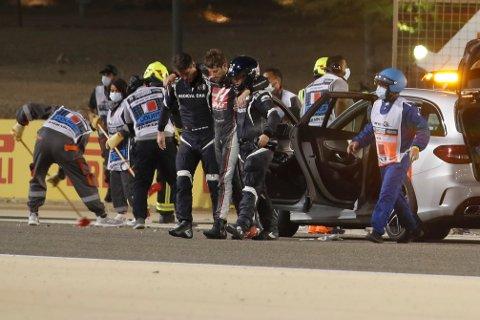 Romain Grosjean støttes av medisinsk personell etter ulykken på Bahrain-banen. Foto: Hamad Mohammed / AP / NTB