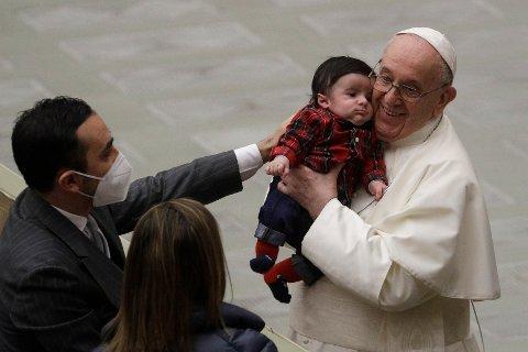 Pave Frans liker å komme nær kolleger og andre troende, og klemte nylig en baby da han møtte ansatte i Vatikanet. Np har to kardinaler i kretsen rundt den katolske kirkens overhode testet positivt for koronaviruset. Foto: Gregorio Borgia / AP / NTB
