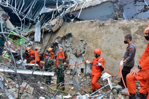 Redningsmannskaper jobbet fredag intenst for å finne overlevende i ruinene og i jordmassene. Her fra en sammenrast bygning tilhørende lokale myndigheter i Mamuju på Sulawesi i Indonesia. Foto: Daus Thobelulu / AP / NTB