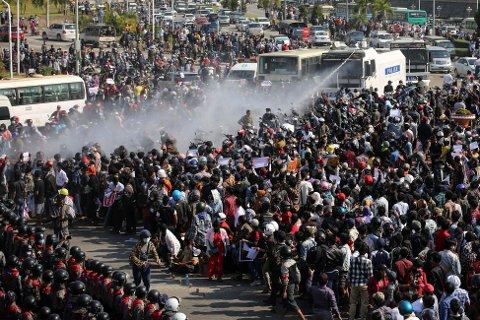 VANNKANONER: Politiet i ferd med å rette vannkanoner mot demonstranter i Naypyitaw i Myanmar mandag.