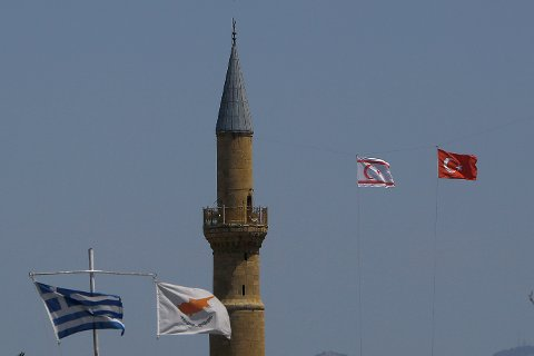 Et gresk og et kypriotisk flagg på sørsiden av delelinjen som går gjennom hovedstaden Nikosia på Kypros. I Nord vaier det tyrkisk-kypriotiske flagget ved siden av det tyrkiske. Minareten i midt på bildet tilhører Selimiye-moskeen, som ligger i den tyrkiske delen av byen. Fram til 1570 var bygningen en kristen katedral. Foto: Petros Karadjias / AP / NTB