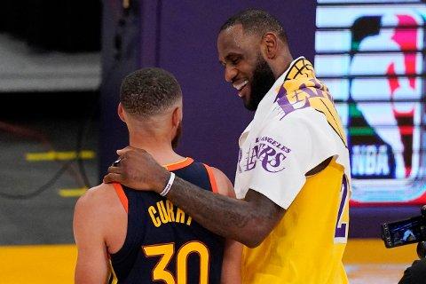 LeBron James trøster Stephen Curry etter å ha trukket lengste strå i duellen mellom de to superstjernene. Han ga sitt Los Angeles Lakers seier i omspillet mot Golden State Warriors og plass i NBA-sluttspillet. Foto: Mark J. Terrill, AP / NTB