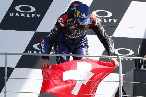 VM-leder i MotoGP Fabio Quartararo med sveitsisk flagg på seierspallen etter seieren i Italias Grand Prix, til minne om talentet Jason Dupasquier som døde av skadene etter at han veltet i Moto3-kvalifiseringen lørdag. Foto: Antonio Calanni, AP / NTB