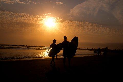 Surfere avkjøler seg som best de kan i heten på Venice Beach i Los Angeles. Foto: Ringo H.W. Chiu / AP / NTB