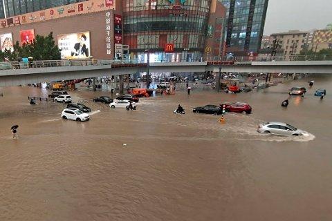 Gater og veier i Zhengzhou sto under vann tirsdag etter at det har falt uvanlig mye regn over den sentrale delen av Kina. Foto: Chinatopix via AP / NTB