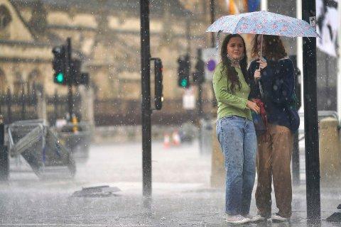 To kvinner forsøker å søke dekning under en paraply ved Parliament Square i sentrum av London søndag.