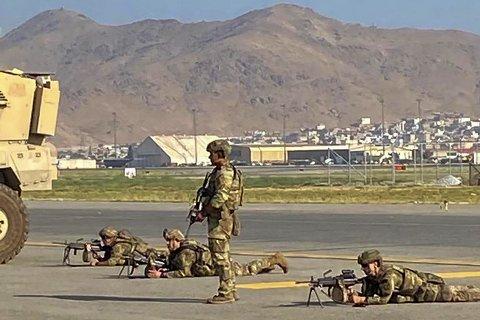 AMERIKANSKE STYRKER: Amerikanske soldater i posisjon for å sikre flyplassen i Kabul mandag. Tusenvis av mennesker strømmet til flyplassen i et desperat forsøk på å unnslippe Taliban-styret.