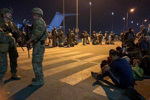 VENTER PÅ TUR: Soldater fra Frankrike står vakt mens franske statsborgere og deres afghanske kolleger venter på transport ut fra Kabul tirsdag.