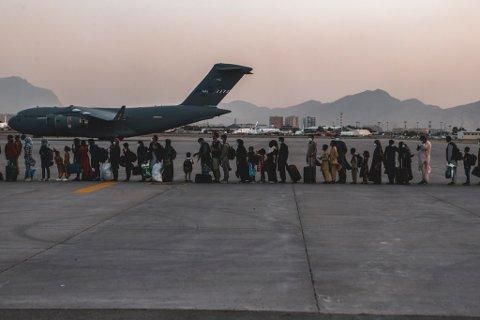 Evakuerte i kø for å gå om bord på et fly på flyplassen i Kabul mandag. Foto: Isaiah Campbell / U.S. Marine Corps / AP / NTB