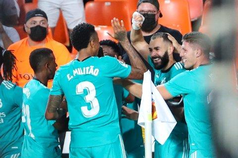 Karim Benzema ble omfavnet av lagkameratene etter å ha snudd kampen i sluttminuttene. Foto: Alberto Saiz / AP / NTB