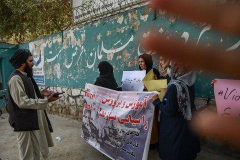 BLE STOPPET: Et medlem av Taliban snakker til de kvinnelige demonstrantene i Kabul mens en annen forsøker å hindre fotografen i å ta bilde.