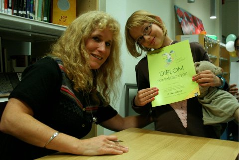 FIKK DIPLOM: Julie Sara Johnsen (8 år) fikk et diplom for å ha lest mange bøker i sommer, og fikk den signert av forfatter Tania Kjeldset.