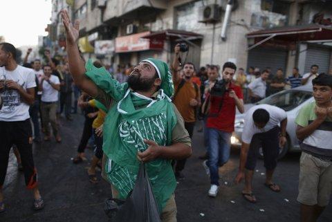 GODE NYHETER: Palestinere kaster godteri i lufta for å feire at en ny våpenhvile er startet.