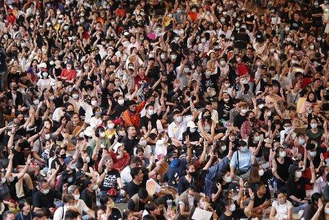 Demonstranter viser protesthilsenen med tre fingre i været under en demonstrasjon i Bangkok i november 2020. Tolv protestledere er nå siktet for brudd på den strenge loven mot kritikk av kongehuset.