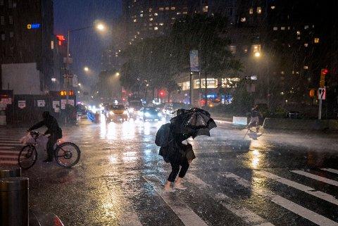KRAFTIG REGN: Fotgjengere søker dekning nær Columbus Circle i New York onsdag, idet orkanen Ida fortsatte å hamre løs på den amerikanske østkysten.