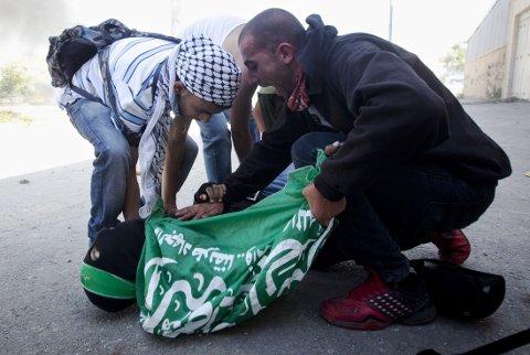 De to palestinske guttene deltok i en demonstrasjon utenfor Ofer-fengselet nær Ramallah på den okkuperte Vestbredden, da de israelske politifolkene åpnet ild med skarp ammunisjon. På bildet har vitner kommet til for å hjelpe den ene.